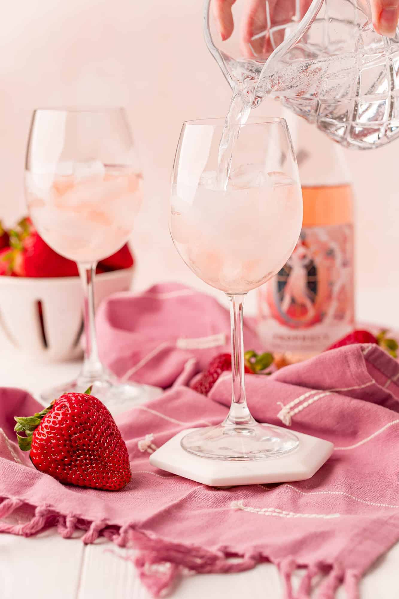 Club soda being poured into a wine glass with ice and rose wine.