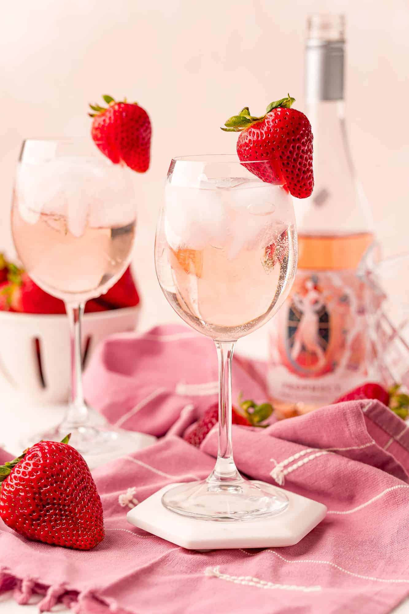 Two stemmed glasses with iced rosé spritzers, garnished with strawberries.