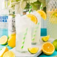 Two glasses of vodka lemonade garnished with orange wedges.