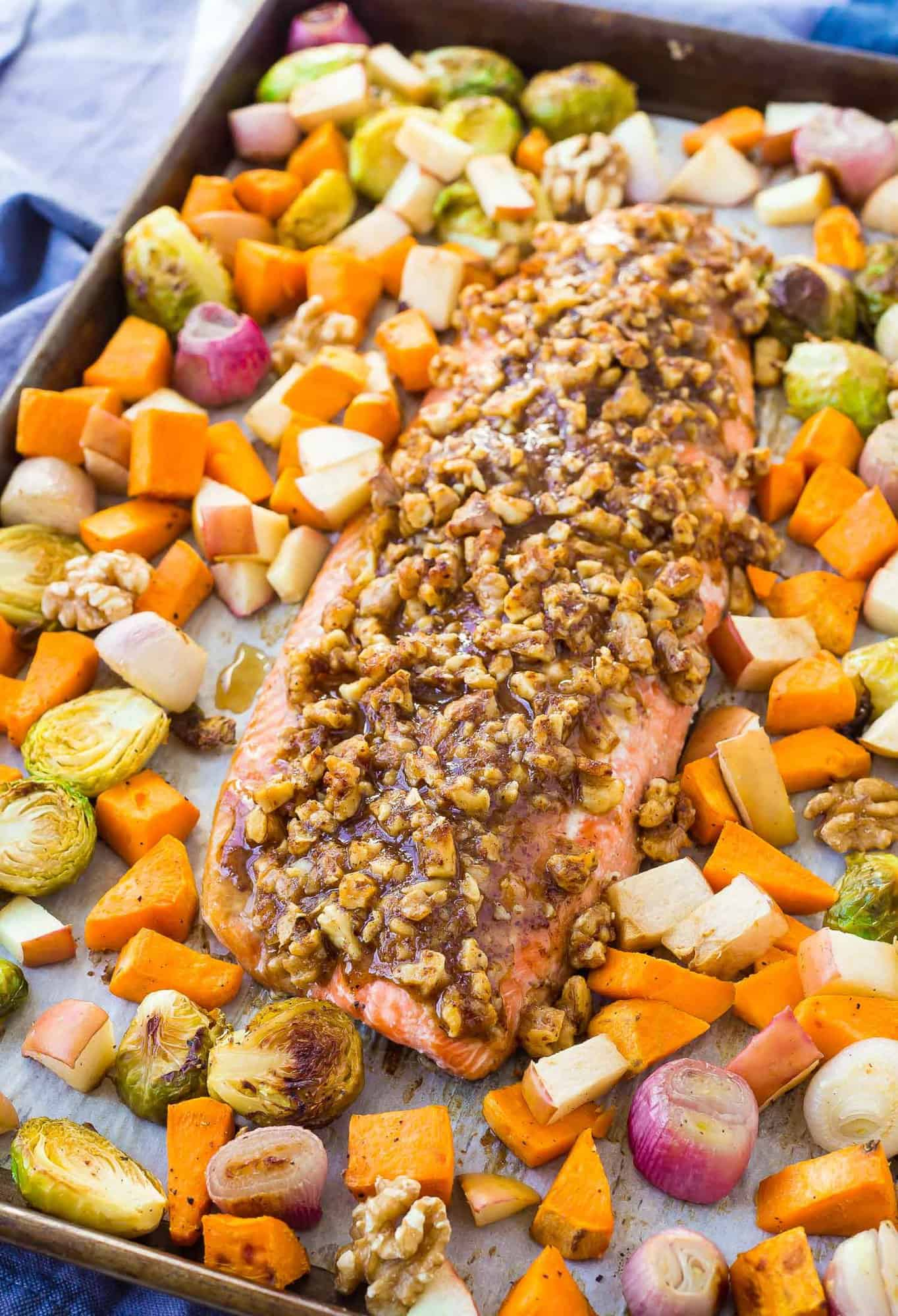 Salmon topped with walnuts and surrounded with colorful vegetables.