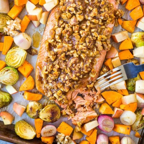 Overhead view of walnut crusted salmon on a sheet pan with vegetables, a fork is flaking salmon.