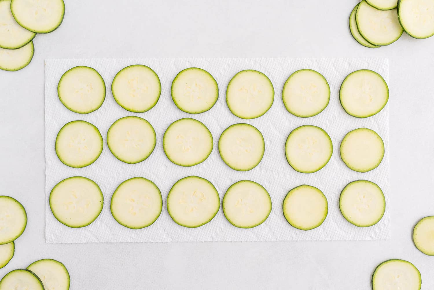 Zucchini slices laid out on a paper towel.