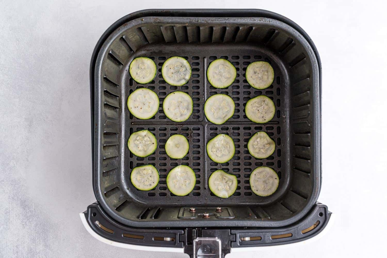 Zucchini in the basket of an air fryer.