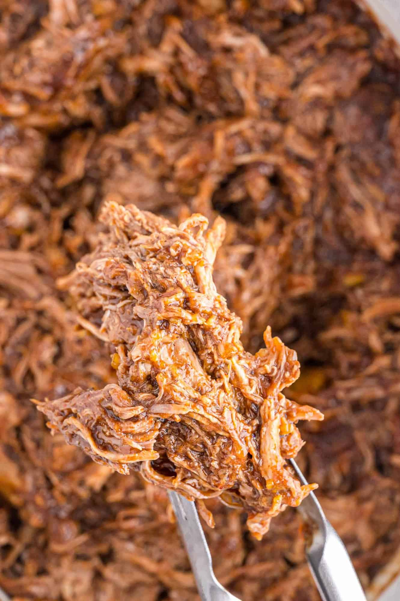 Pulled pork on tongs.