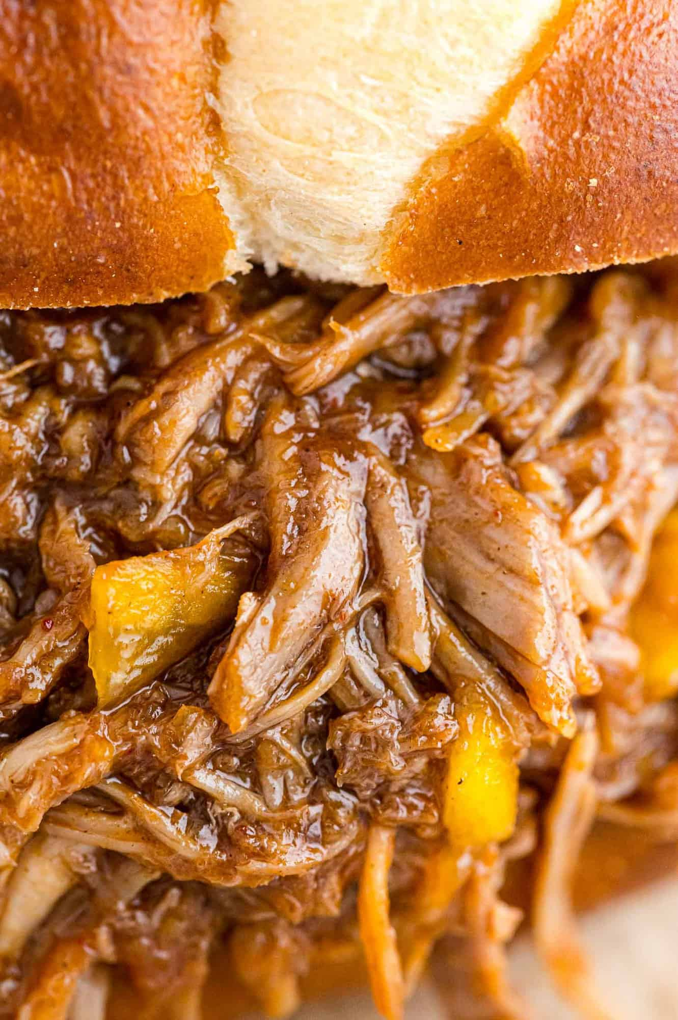 Very close up view of pulled pork with mango, on a bun.