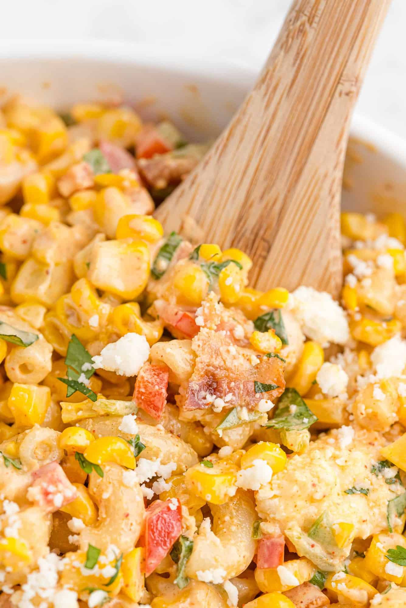 Close up of corn pasta salad with a wooden spoon in it.