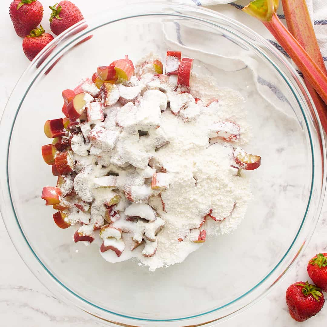 Rhubarb and strawberries in a glass bowl with flour mixture on top.