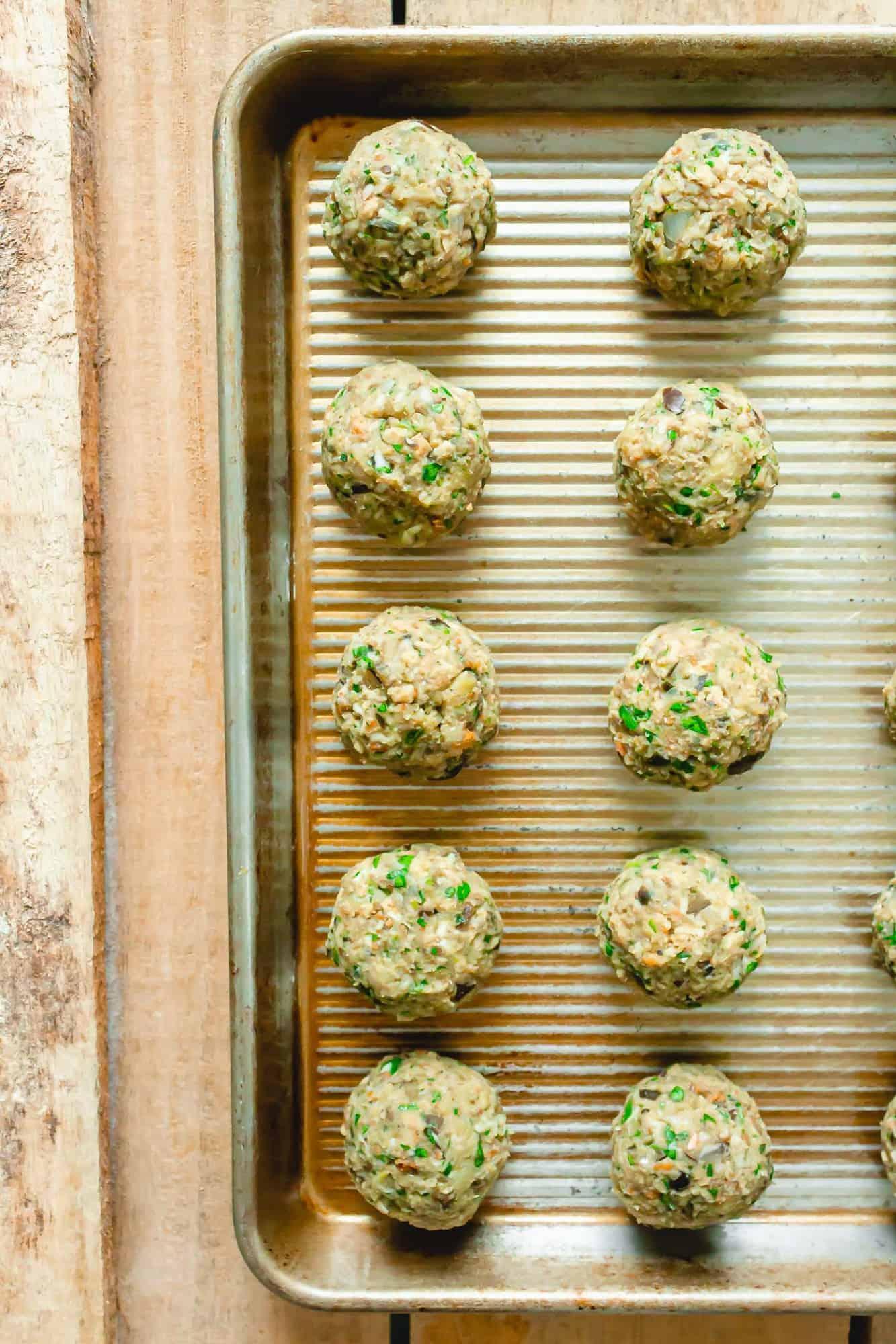 Uncooked vegetarian meatballs on a baking sheet.