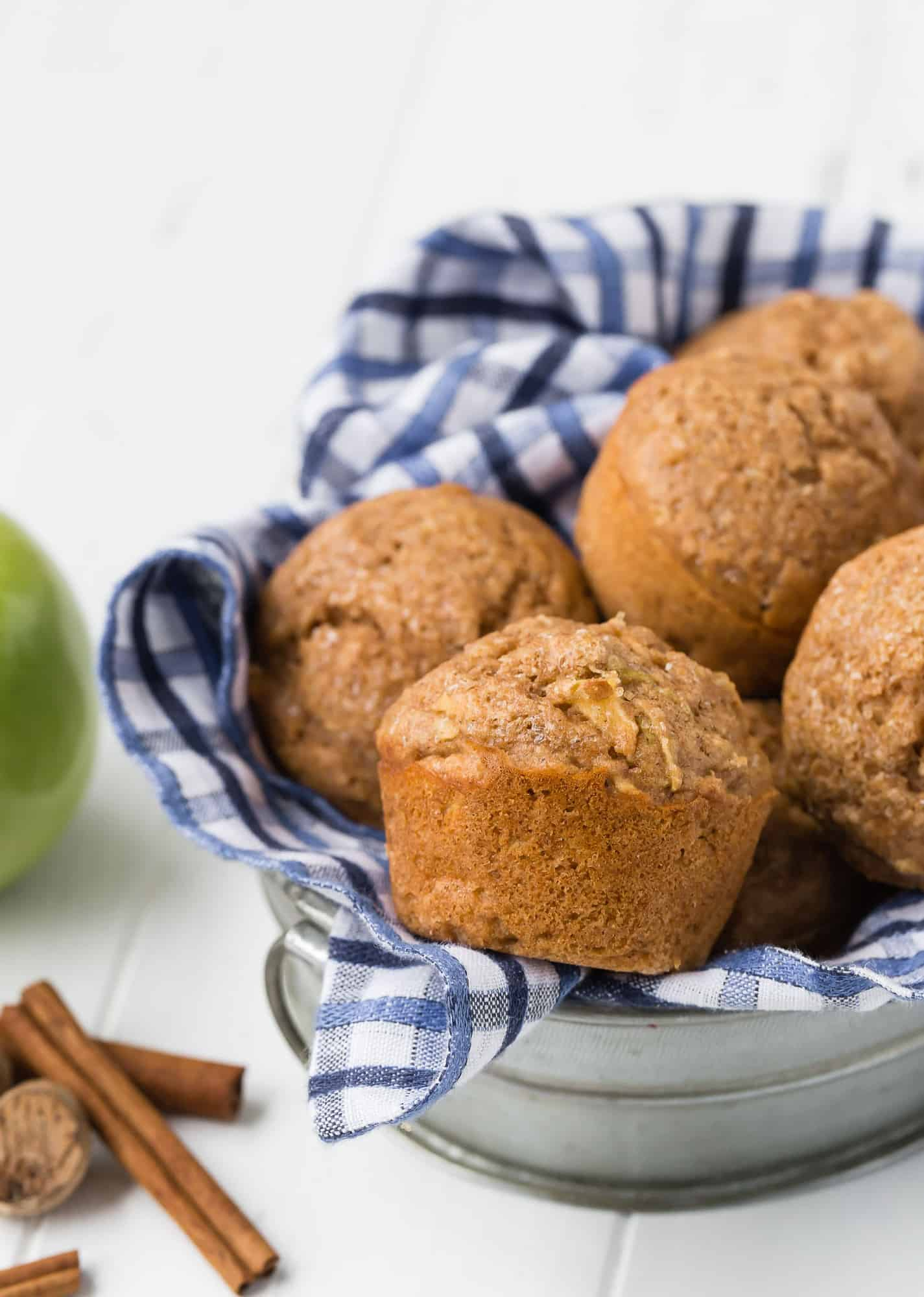 Whole wheat apple muffins in a metal basket with a blue and white checkered towel.
