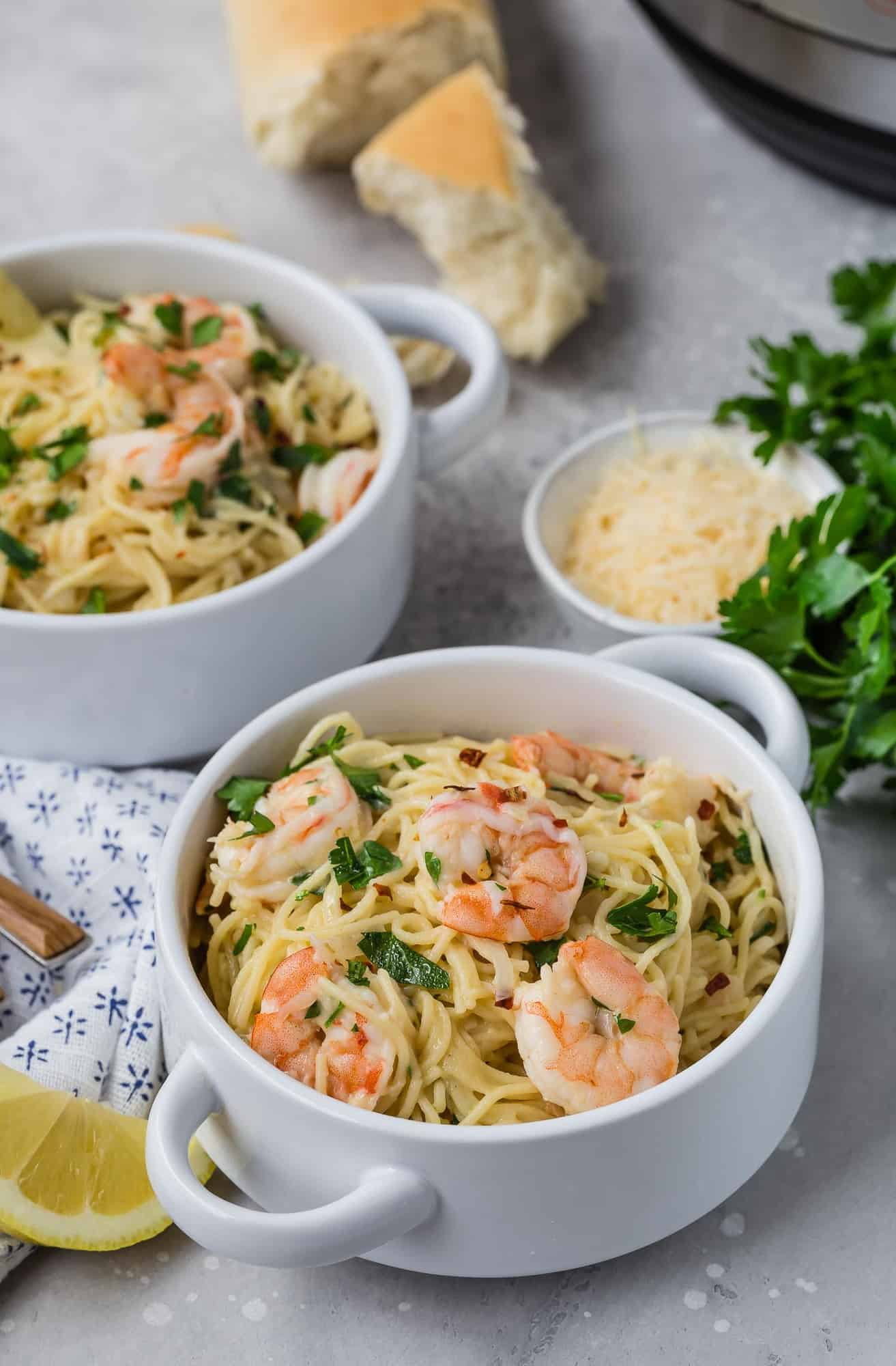 Two bowls of shrimp scampi pasta, bread, cheese, and parsley in background.