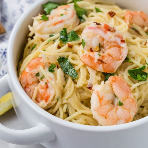 Shrimp and pasta in a white bowl, garnished with fresh parsley.