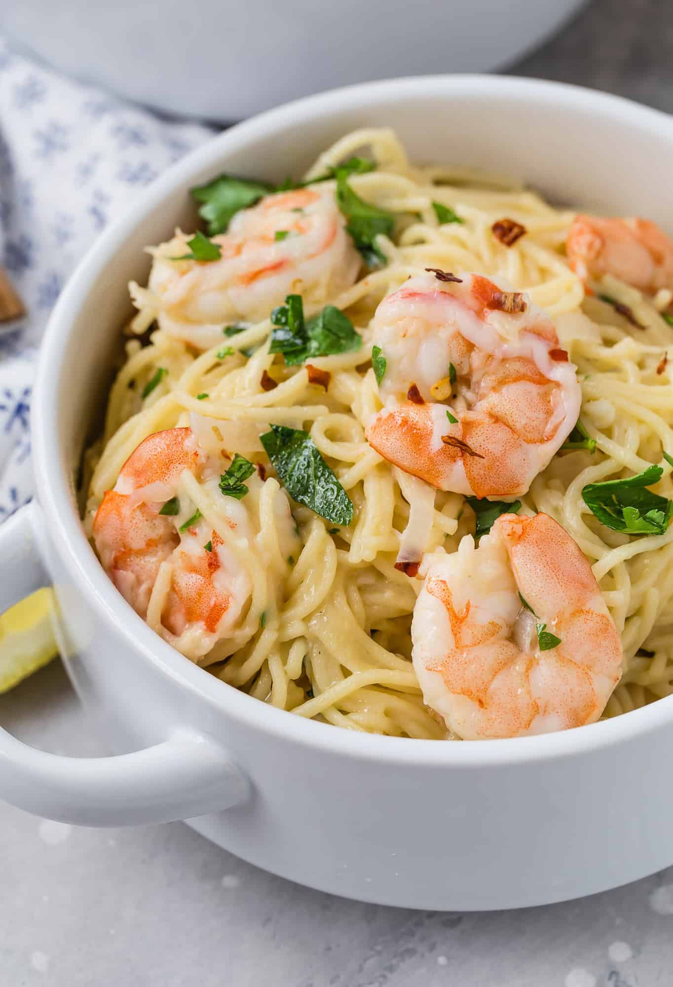 Shrimp scampi pasta in a white two-handled bowl.