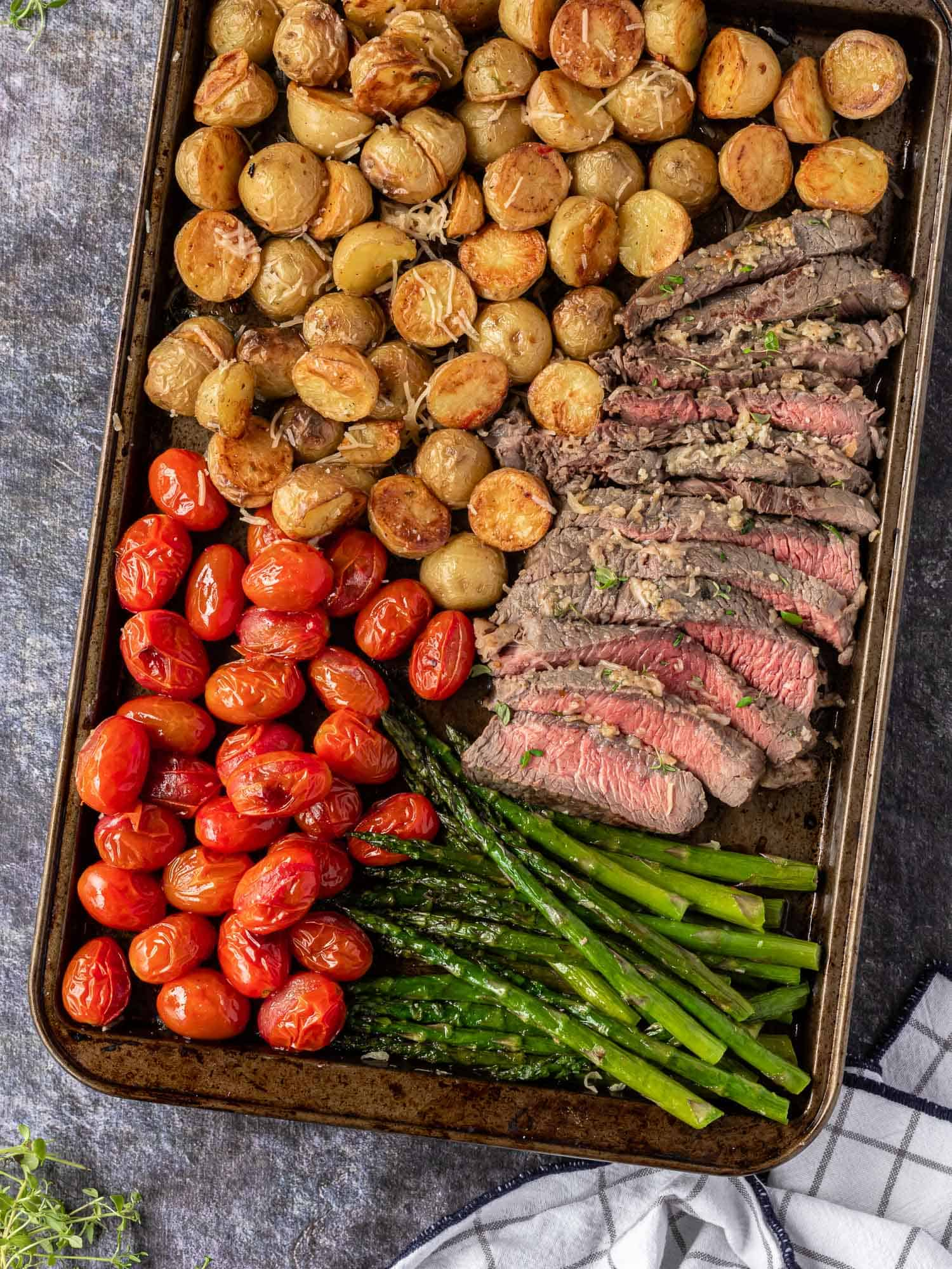 Cut steak, pink inside, on a sheet pan with tomatoes, potatoes, asparagus.