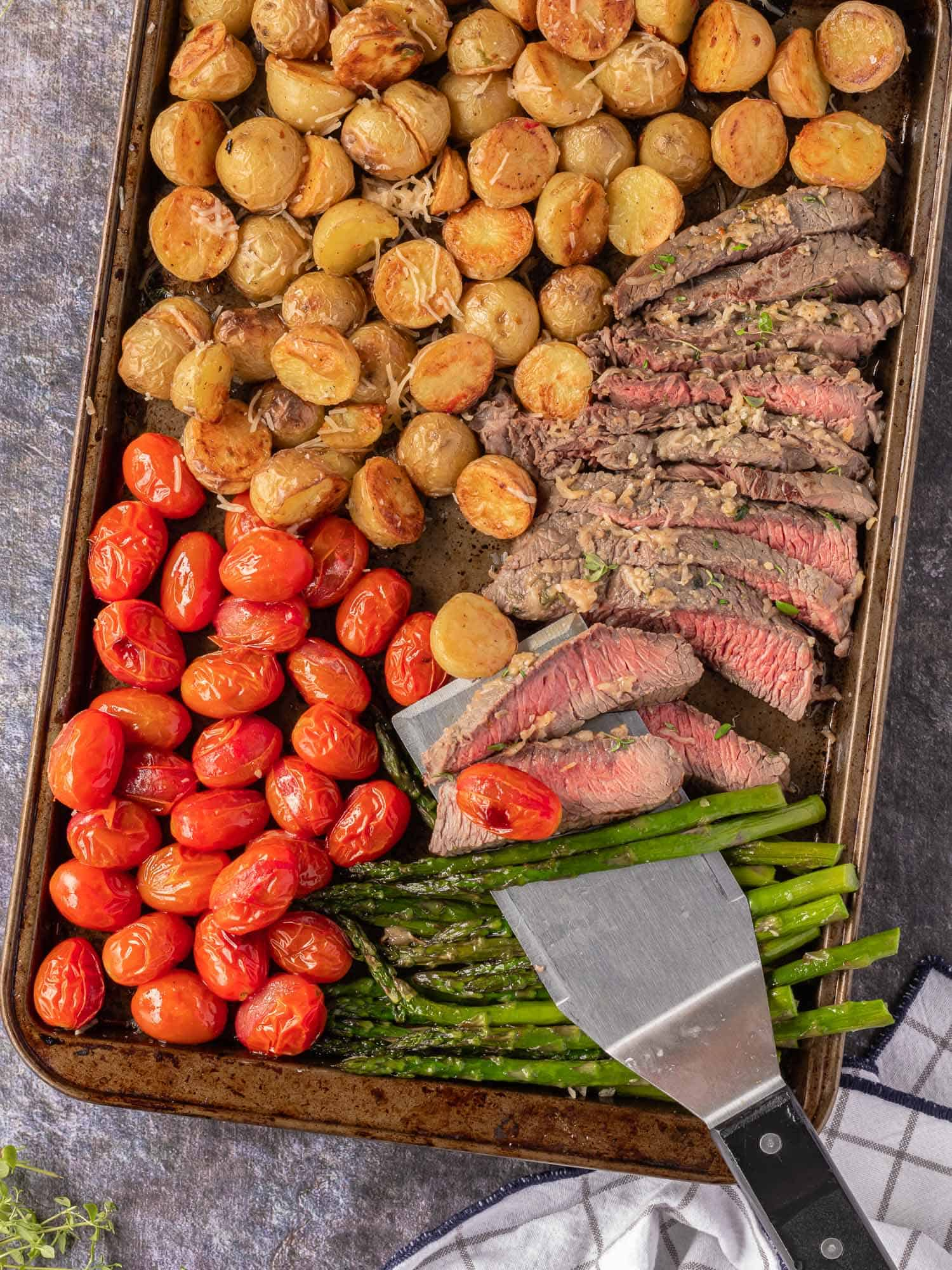 Steak on a spatula, surrounded by other food: tomatoes, asparagus, and potatoes.