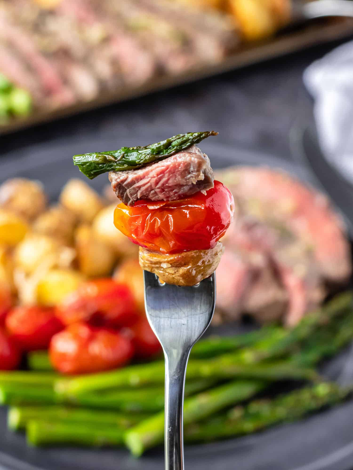 Steak on a fork with a tomato, potato, and asparagus.