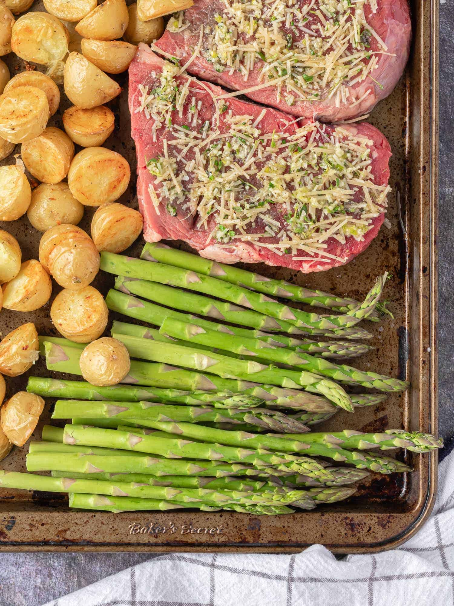 Uncooked steak and vegetables on a sheet pan.