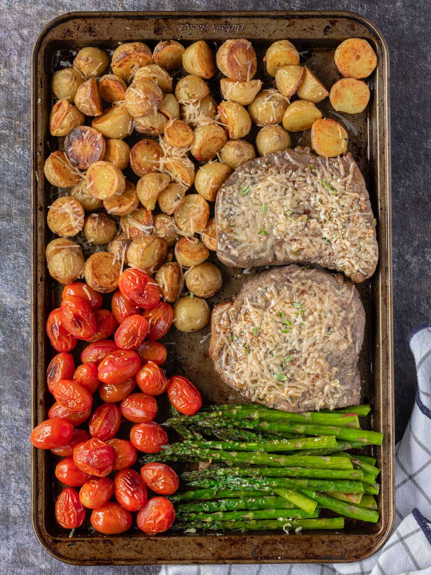 Cooked steak and vegetables on a large sheet pan.