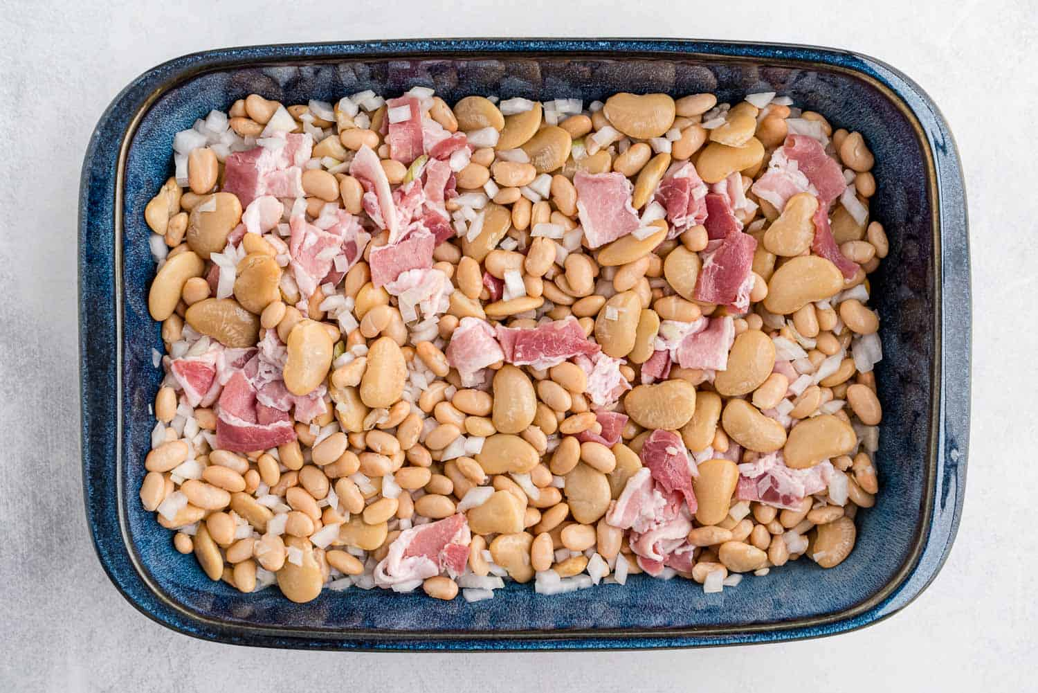 Beans, uncooked bacon, and onions in a baking dish.