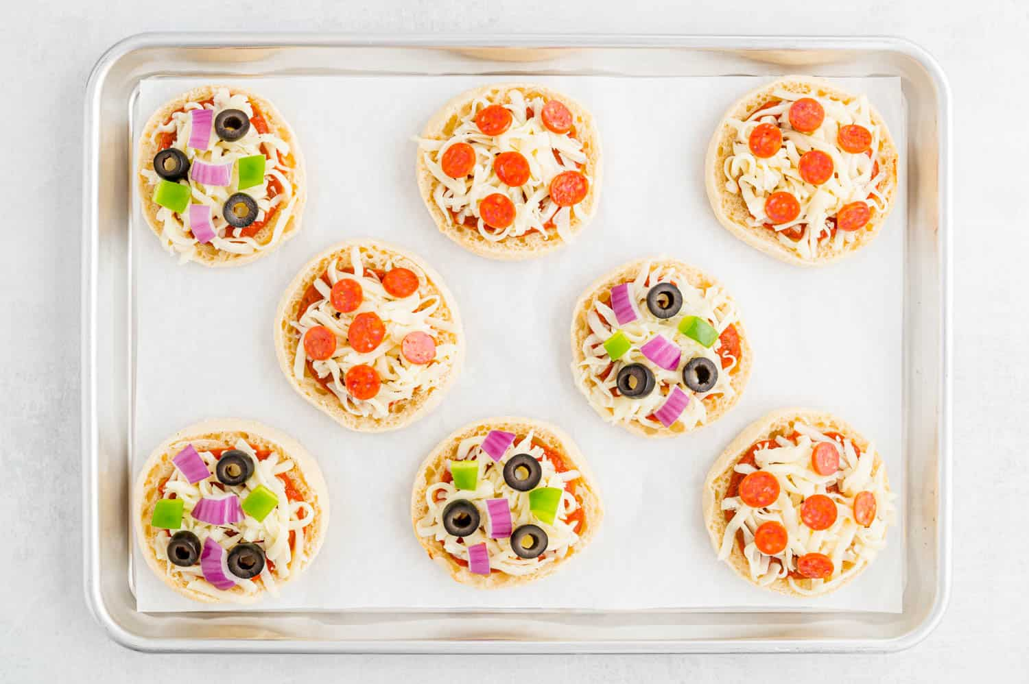 Uncooked english muffin pizzas on a sheet pan.