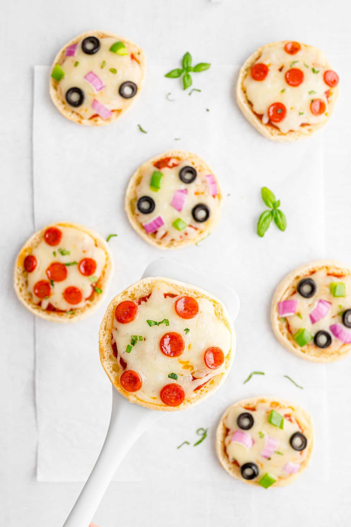 English muffin pizza on a spatula, others visible on a sheet pan.