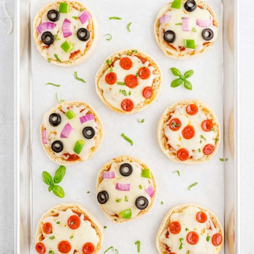 Overhead view of english muffin pizzas on a parchment paper lined baking sheet.