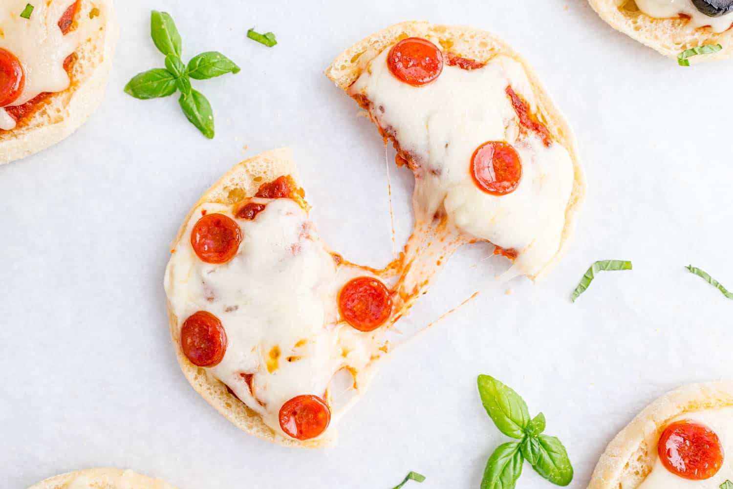 Pepperoni topped english muffin pizza, split in half with a cheese connecting two halves.