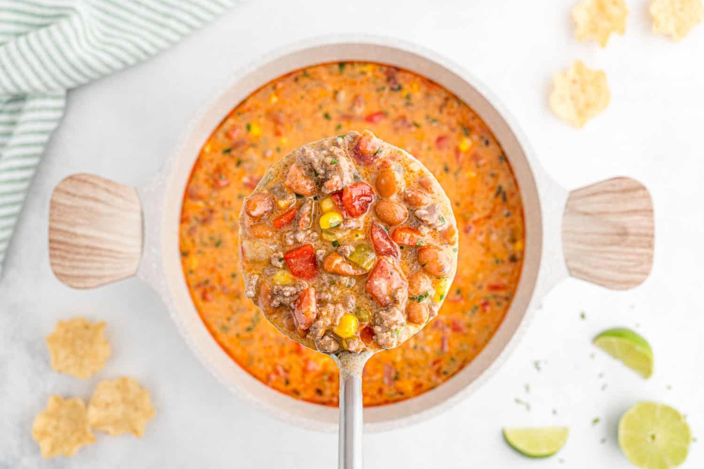 Ladle of creamy queso chili over a pan of more chili.