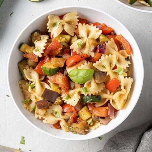 Bowl of pasta salad with bowtie pasta and grilled vegetables.