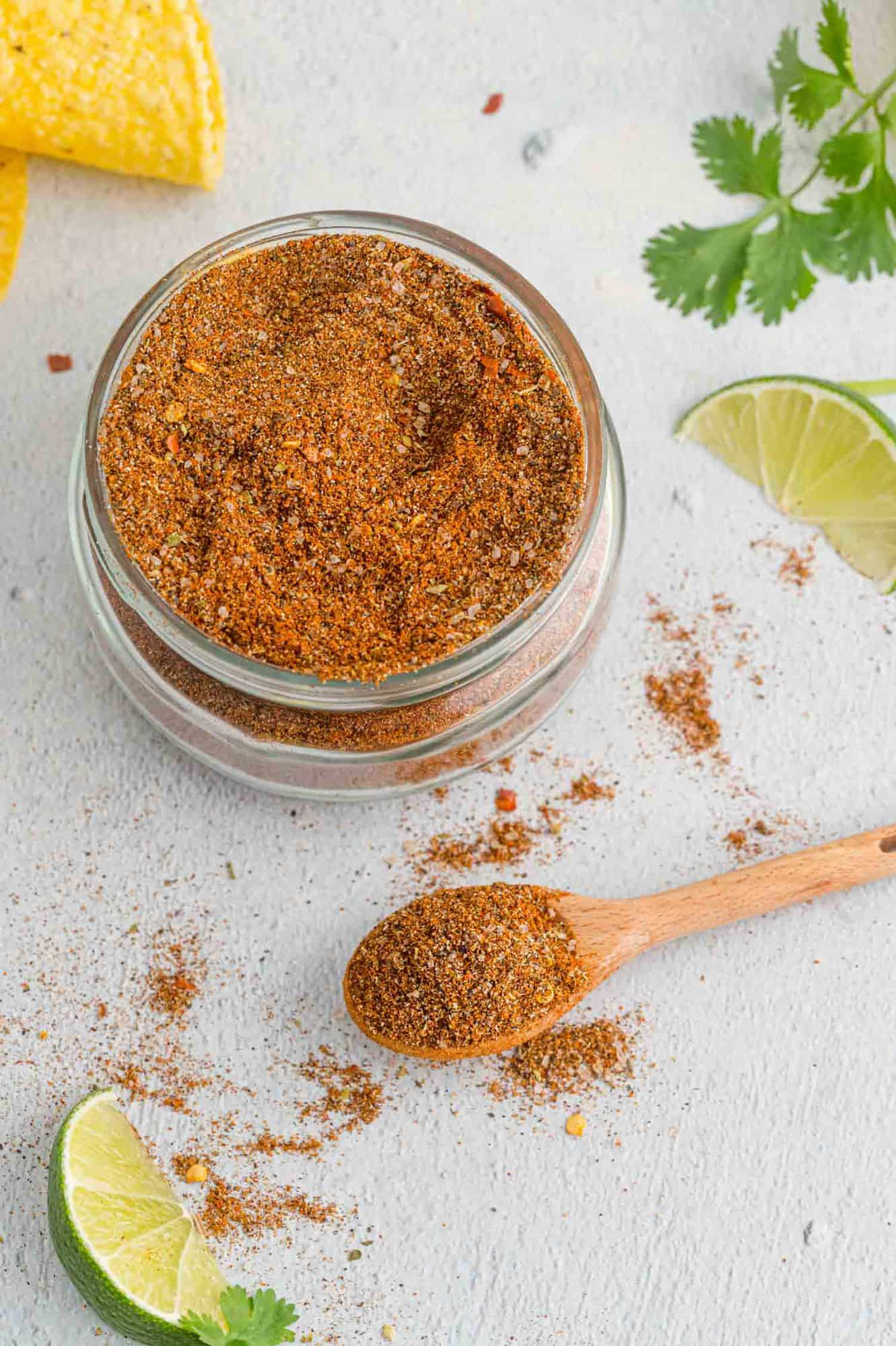 Taco seasoning in a small jar, a wooden spoonful nearby, and a lime wedge.