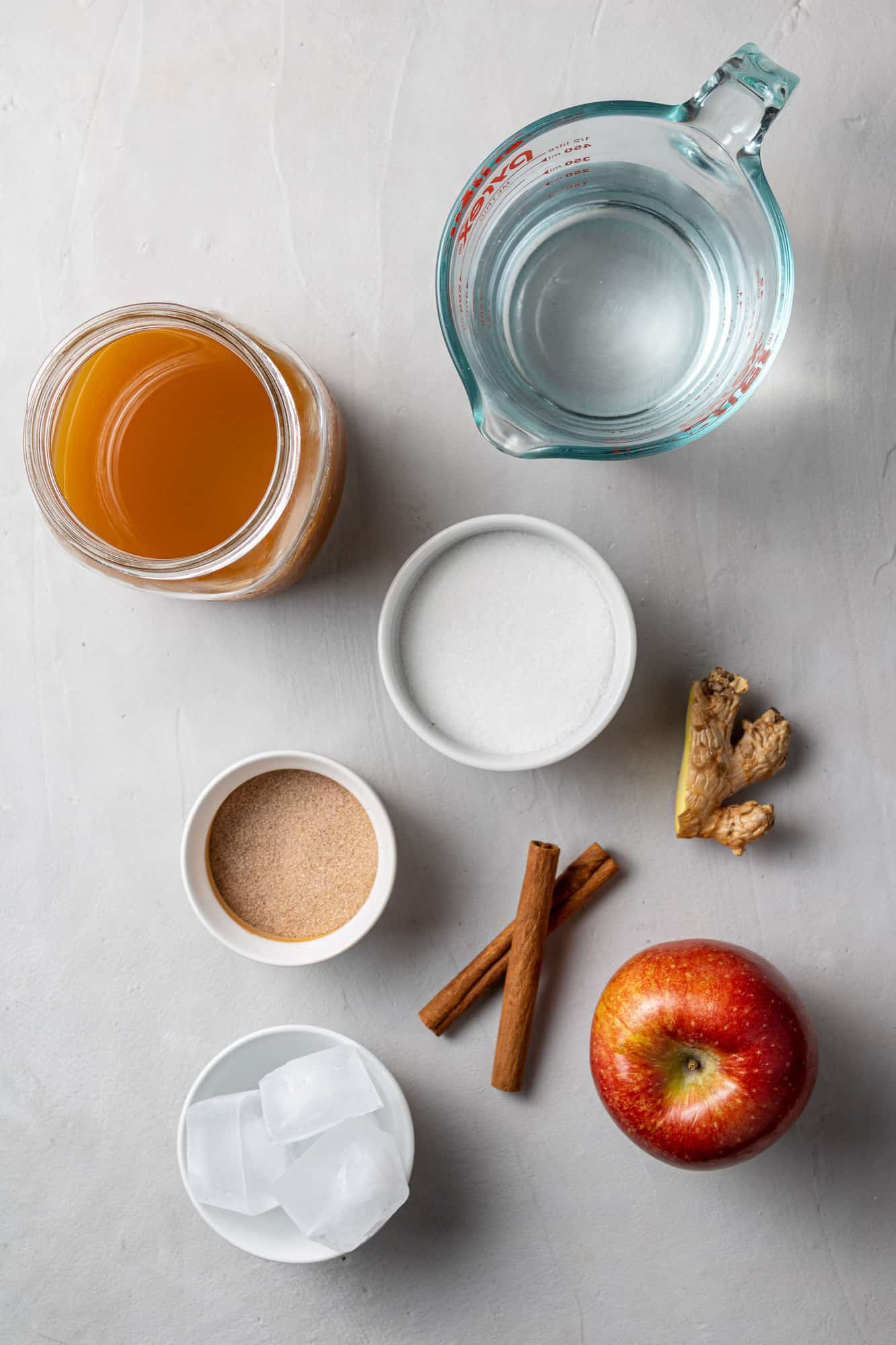 Overhead view of cider, water, cinnamon sticks, ginger, apple, and cinnamon sugar.