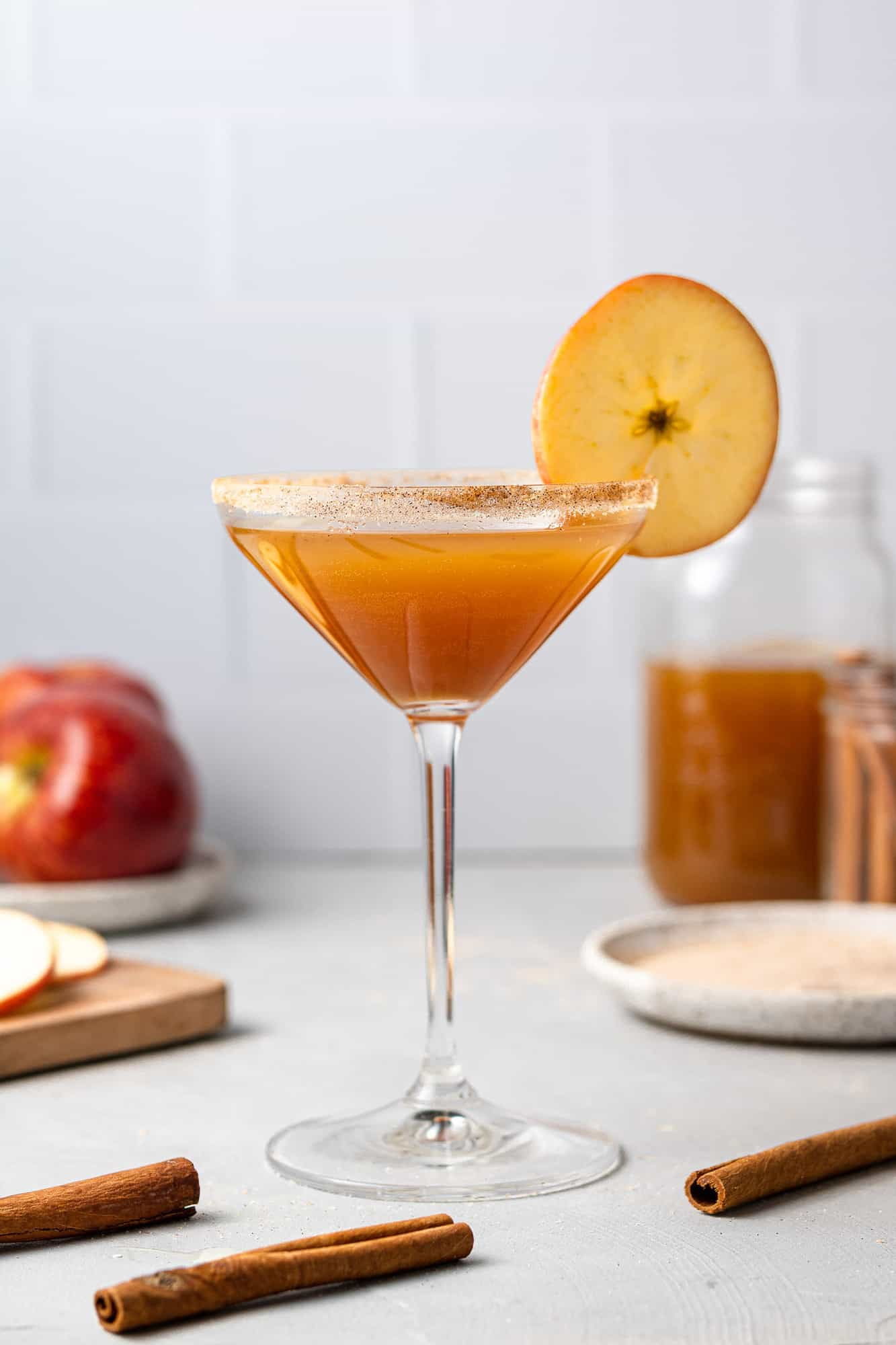 An apple cider based cocktail in a martini glass against a white background.