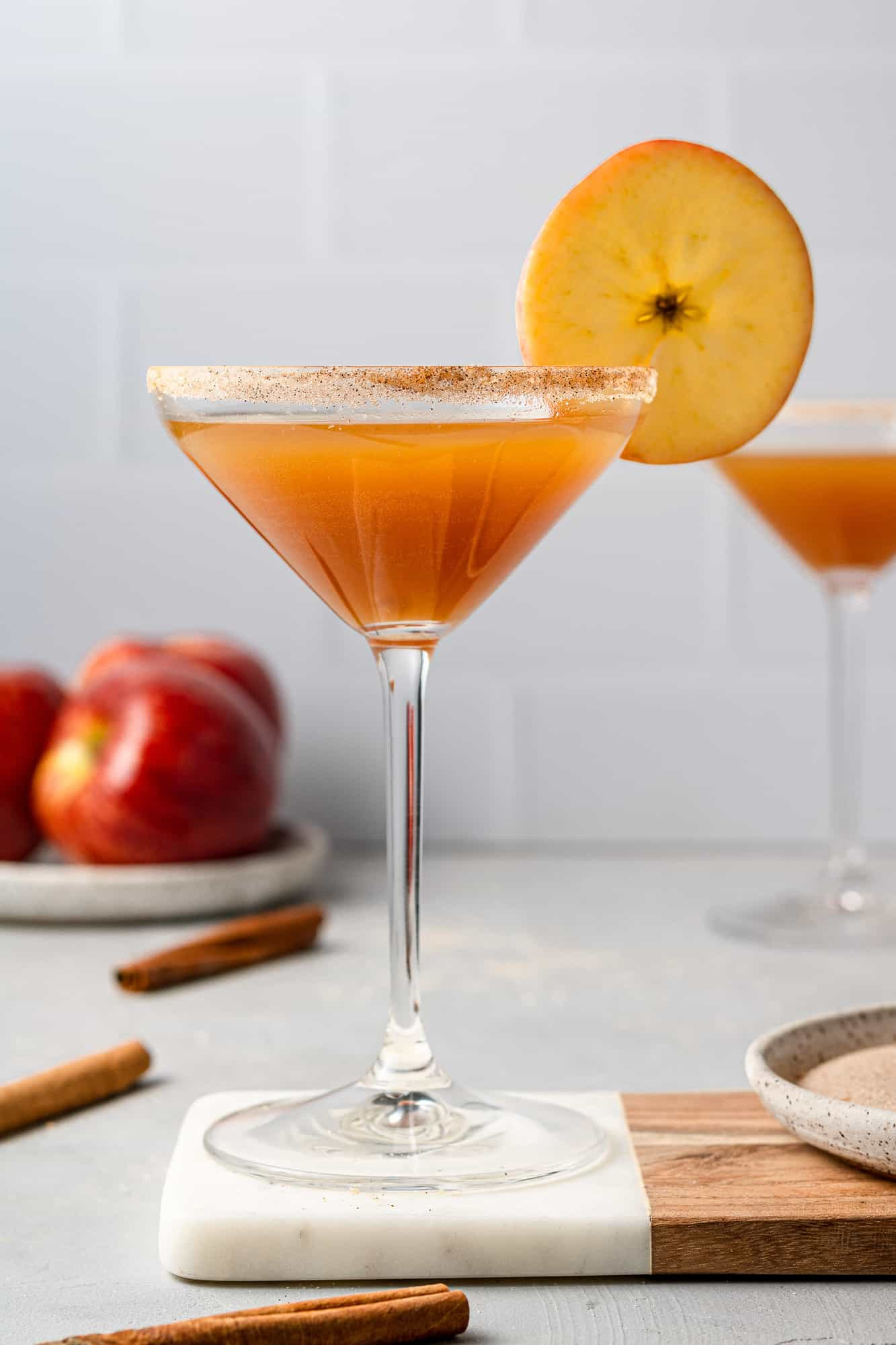 Martini glass filled with apple cider and simple syrup, garnished with cinnamon sugar and an apple slice.
