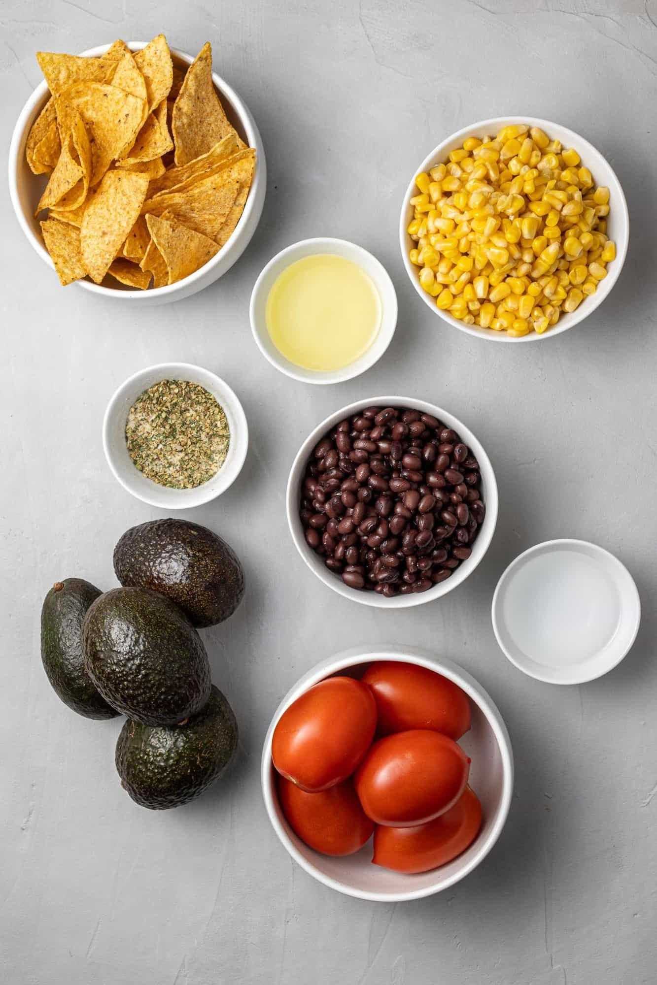 Overhead view of ingredients: tomatoes, corn, avocados, beans, chips.