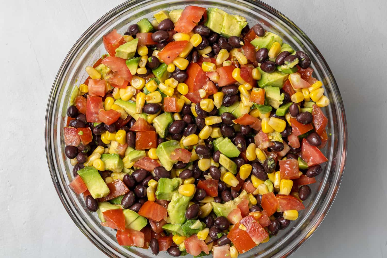 Chopped vegetables, avocado, and beans in a white glass bowl.