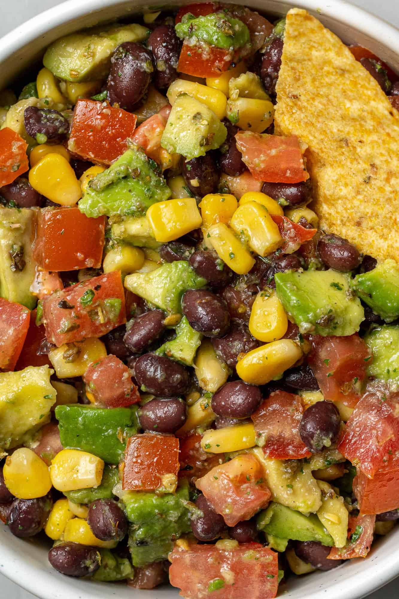 Close up view of salad with black beans, avocado, corn, tomatoes.