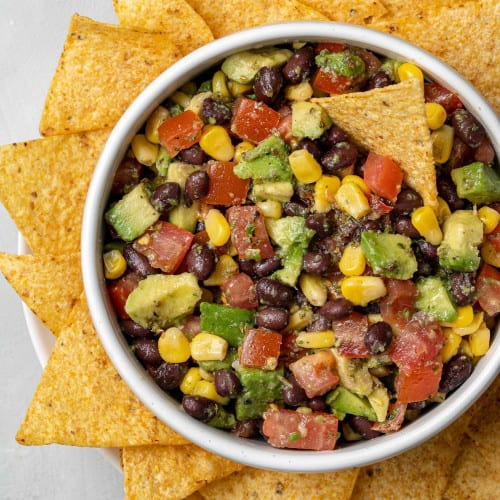 Overhead view of black bean, avocado, and corn salad with tortilla chips.