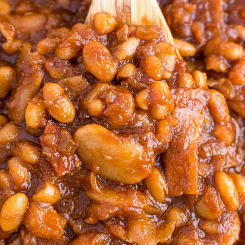 Close up view of baked beans on a wooden spoon.