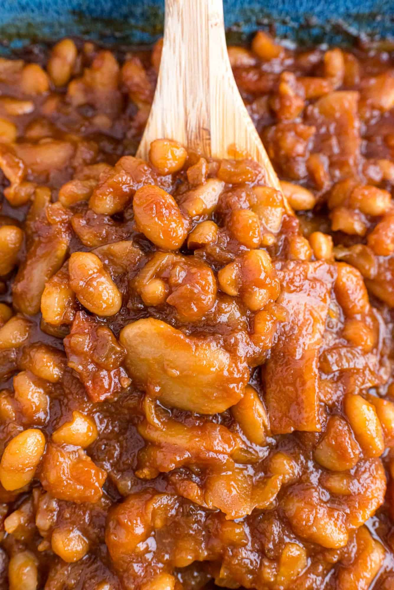 Close up of homemade baked beans with bacon on a wooden spoon.