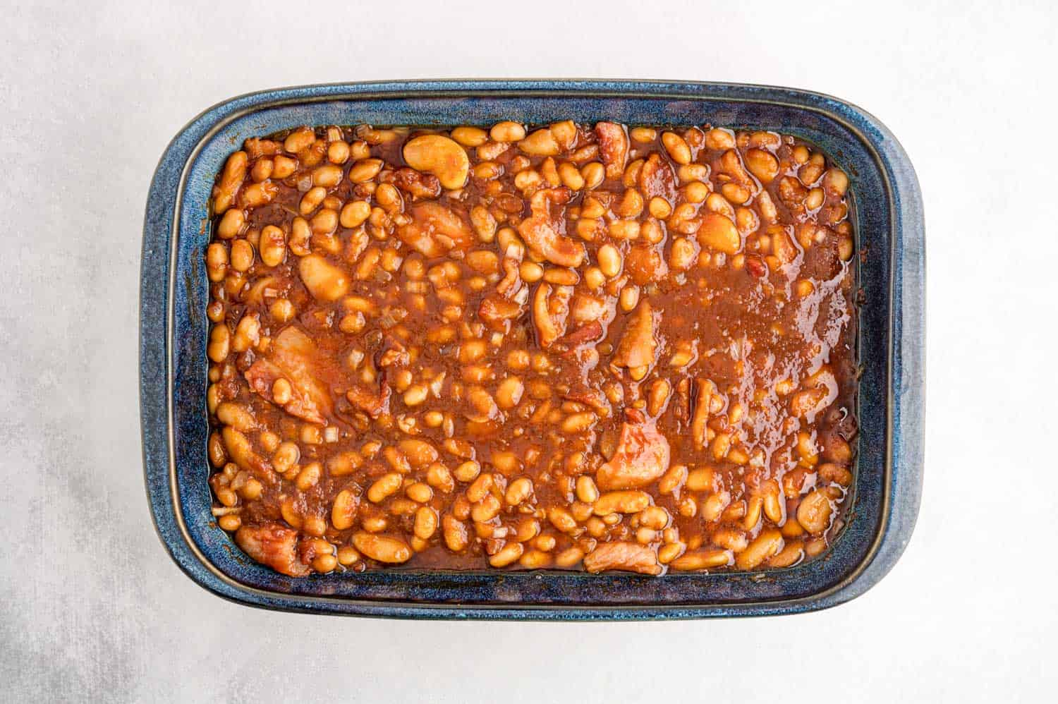 Uncooked beans in a blue casserole dish.