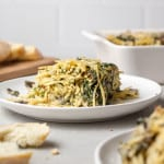 Baked spaghetti with spinach on a small round white plate.