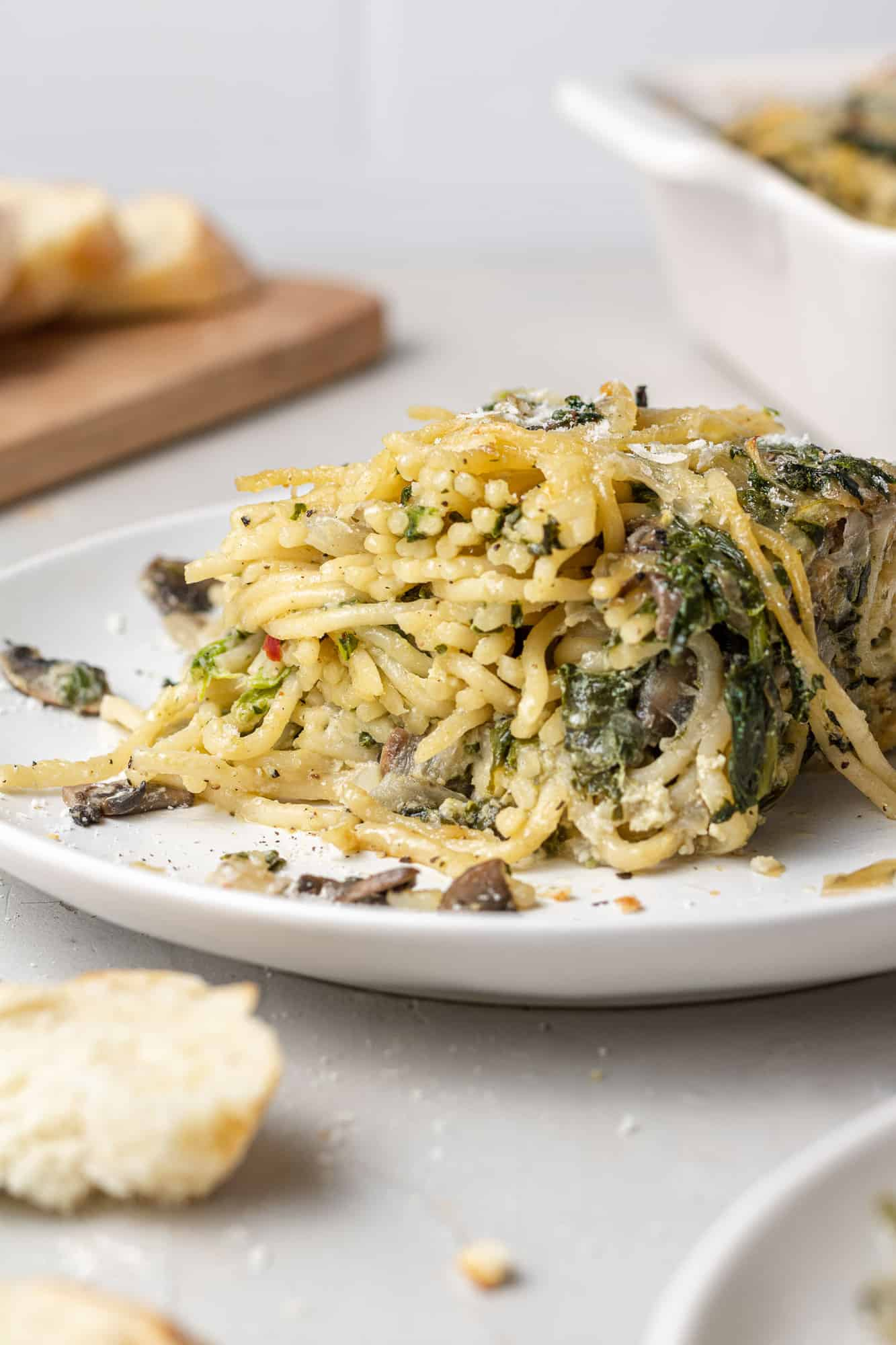 Close up of spaghetti mixed with spinach, cheese, and mushrooms on a small white plate.