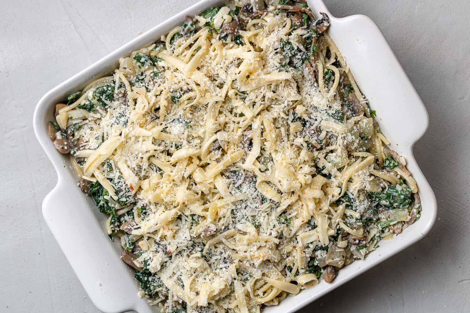 Spinach spaghetti topped with cheese.