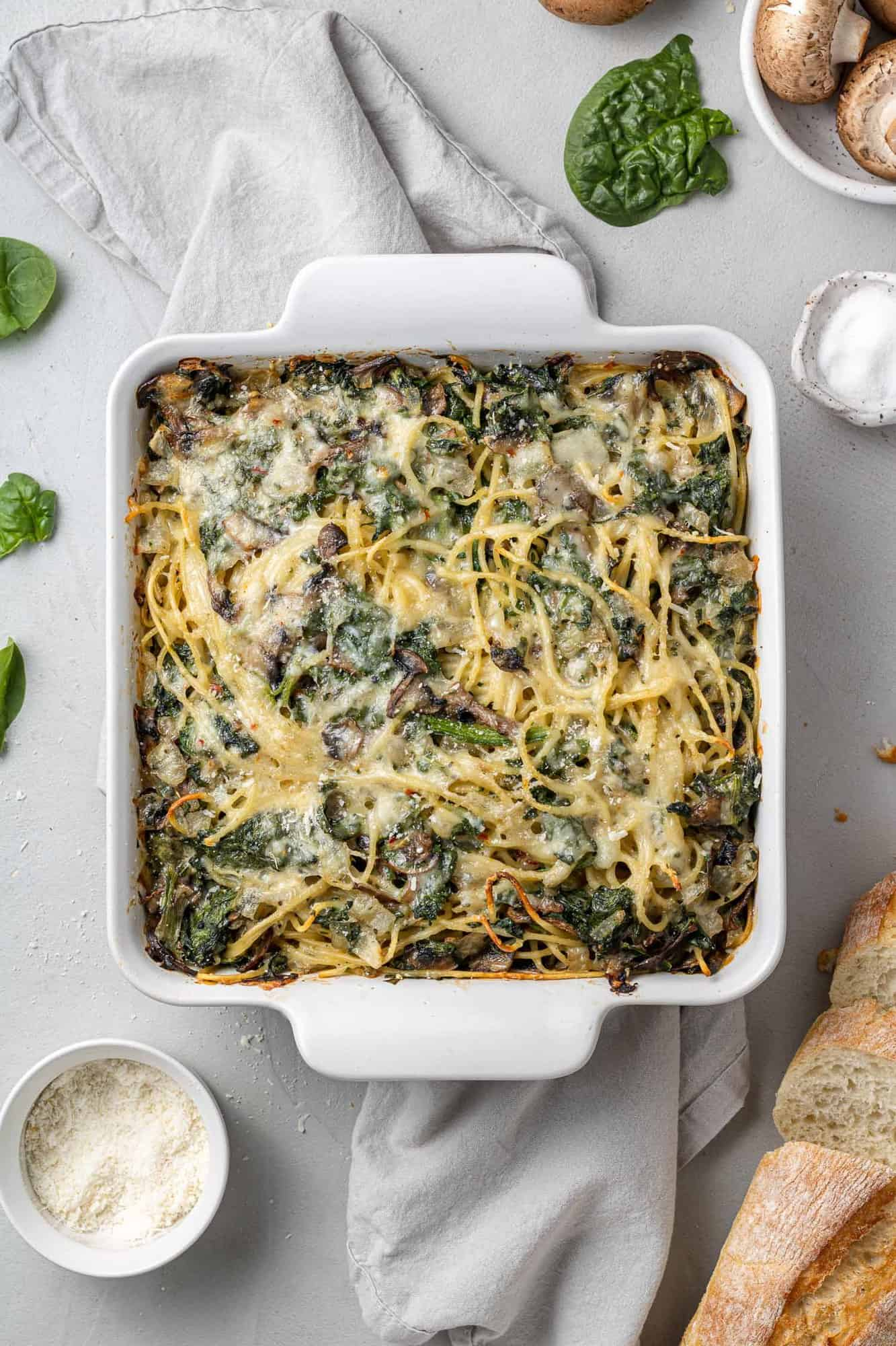 Baked spaghetti with spinach and mushrooms in a square white baking dish.