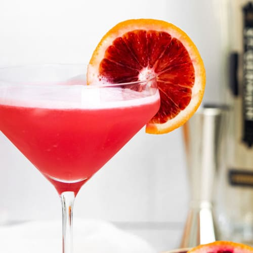 Close up of martini glass with bright red cocktail garnished with blood orange.