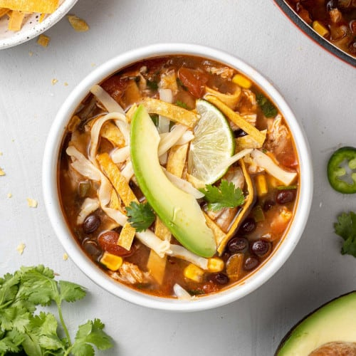 Overhead view of a bowl of chicken tortilla soup topped with avocado, tortilla strips, and cheese.