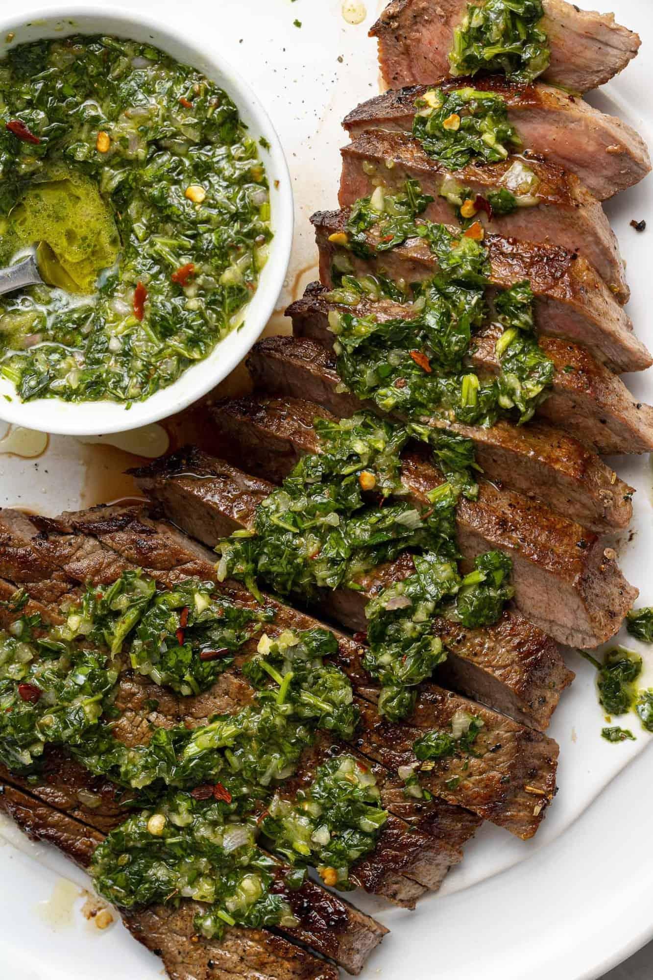 Close up of chimichurri on sliced steak.