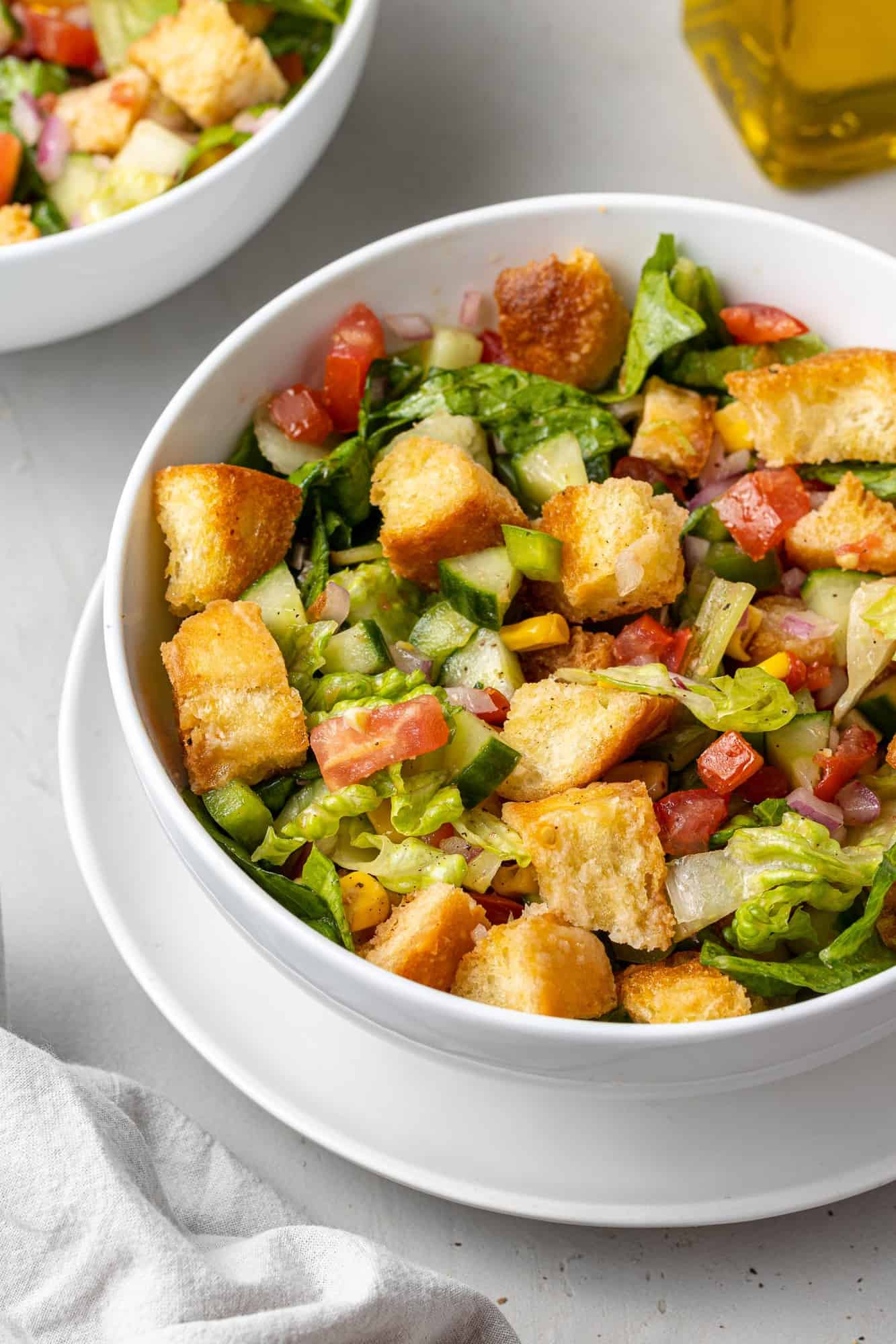 White bowl with chipped salad in it, including corn, tomatoes, peppers and croutons.