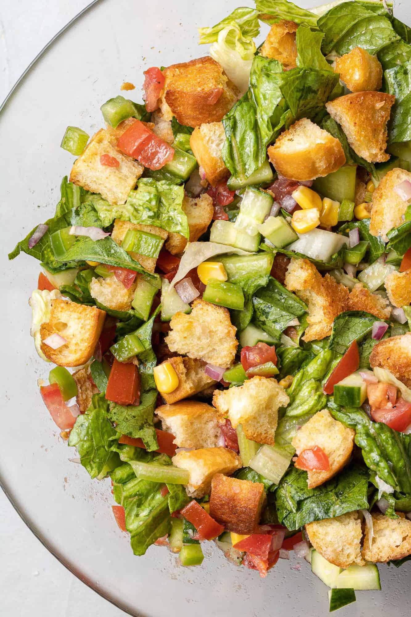 Close up gazpacho chopped salad in a clear bowl.