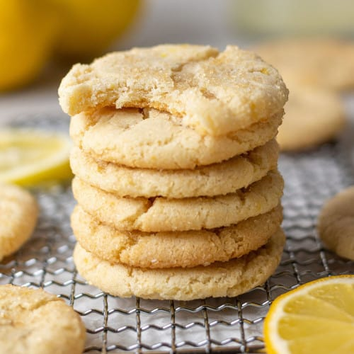 Lemon cookies in stack, the top one with a bite taken out of it.