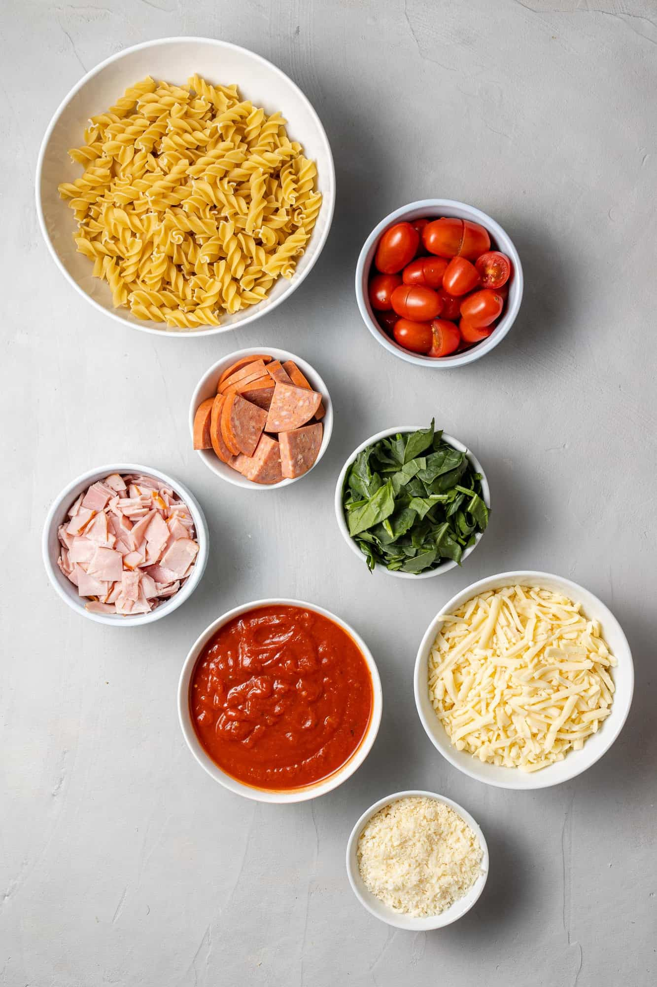 Overhead view of ingredients needed including pasta, tomatoes, ham, pepperoni.